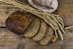 Φραντζόλες του ψωμιού, φέτες του ψωμιού και αυτιά του σιταριού στο ξύλινο υπόβαθρο Αγροτική και αγροτική έννοια κλείστε επάνω Στοκ Εικόνα