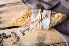 Φραντζόλα ολόκληρου του ψωμιού σίτου σίκαλης που τυλίγεται στο έγγραφο περγαμηνής για την πετσέτα λινού, ξύλινο υπόβαθρο σανίδων Στοκ Εικόνες