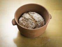 Φραντζόλα σίκαλης του ψωμιού που ψήνεται σε ένα κύπελλο ψησίματος αργίλου Στοκ εικόνα με δικαίωμα ελεύθερης χρήσης