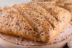 Φραντζόλα του ψωμιού δημητριακών στον ξύλινο πίνακα με το άλας γύρω Στοκ Εικόνα