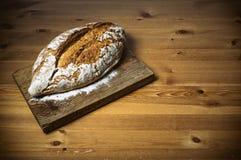 Φραντζόλα του ψωμιού στον καφετή ξύλινο τέμνοντα πίνακα Στοκ φωτογραφία με δικαίωμα ελεύθερης χρήσης