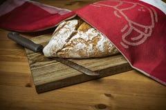 Φραντζόλα του ψωμιού στον ξύλινο τέμνοντα πίνακα Στοκ Εικόνα