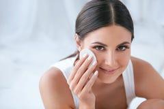 Φροντίδα δέρματος προσώπου Όμορφη γυναίκα που αφαιρεί Makeup με το μαξιλάρι βαμβακιού στοκ εικόνες