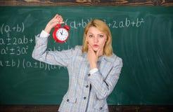 Φροντίζει για την πειθαρχία Ξυπνητήρι λαβής δασκάλων γυναικών Σχολικός ομιλητής κοριτσιών Τι ώρα είναι Πρόγραμμα μαθημάτων στοκ εικόνες με δικαίωμα ελεύθερης χρήσης