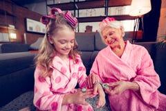 Φροντίζοντας ακτινοβολώντας γιαγιά που δίνει το χαριτωμένα δαχτυλίδι και το βραχιόλι κοριτσιών της στοκ εικόνες με δικαίωμα ελεύθερης χρήσης