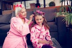 Φροντίζοντας γιαγιά που βάζει τα ρόλερ τρίχας στην τρίχα του χαριτωμένου μικρού κοριτσιού της στοκ εικόνα με δικαίωμα ελεύθερης χρήσης