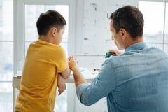Φροντίζοντας γιος διδασκαλίας πατέρων πώς να χρησιμοποιήσει το μέτρο ταινιών Στοκ Εικόνες