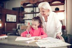 Φροντίζοντας γκρίζος-μαλλιαρή γιαγιά που αγκαλιάζει τις χαριτωμένες επιστολές γραψίματος κοριτσιών της στοκ φωτογραφίες