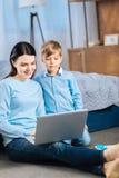 Φροντίζοντας μητέρα και τα κινούμενα σχέδια προσοχής γιων της on-line Στοκ Φωτογραφίες