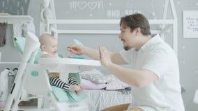 Φροντίζοντας μπαμπάς με το ταΐζοντας νήπιο κινητών τηλεφώνων bsaby απόθεμα βίντεο