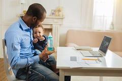 Φροντίζοντας μπαμπάς που κρατά το μπουκάλι του γιων και μωρών Στοκ Φωτογραφία