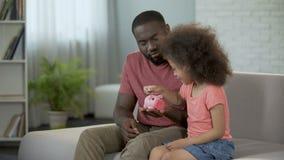 Φροντίζοντας παιδί διδασκαλίας πατέρων για να κερδίσει χρήματα, που βάζουν τα νομίσματα στη piggy τράπεζα απόθεμα βίντεο