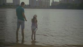 Φροντίζοντας πατέρας και χαριτωμένη αλιεία κορών στον ποταμό απόθεμα βίντεο