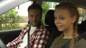 Φροντίζοντας πατέρας που διδάσκει τη νέα κόρη για να οδηγήσει το αυτοκινητικό, νέο οδηγώντας σχολείο απόθεμα βίντεο