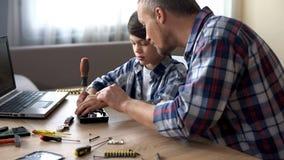 Φροντίζοντας πατέρας που διδάσκει το μικρό γιο του για να επισκευάσει την κίνηση σκληρών δίσκων στο σπίτι, χόμπι στοκ φωτογραφία με δικαίωμα ελεύθερης χρήσης