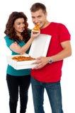 Φροντίζοντας φίλη που κάνει το φίλο της να φάει την πίτσα Στοκ Εικόνες