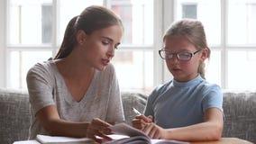 Φροντίζοντας mom δάσκαλος που βοηθά την κόρη παιδιών με την εργασία στο σπίτι απόθεμα βίντεο