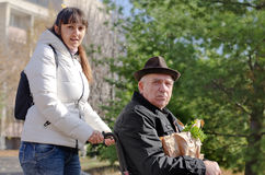 Φροντιστής που βοηθά ένα άτομο σε μια αναπηρική καρέκλα Στοκ Φωτογραφίες