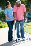 Φροντιστής που βοηθά το ανώτερο άτομο με το πλαίσιο περπατήματος