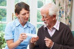 Φροντιστής που βοηθά το ανώτερο άτομο με το φάρμακο στοκ φωτογραφία με δικαίωμα ελεύθερης χρήσης