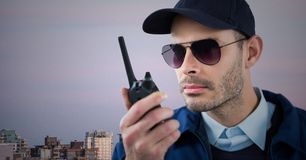 Φρουρά ασφάλειας με την ομιλούσα ταινία walkie ενάντια στον ορίζοντα και τον πορφυρό ουρανό Στοκ Φωτογραφία