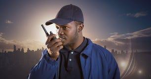 Φρουρά ασφάλειας με την ομιλούσα ταινία walkie ενάντια στον ορίζοντα και το ηλιοβασίλεμα Στοκ εικόνα με δικαίωμα ελεύθερης χρήσης