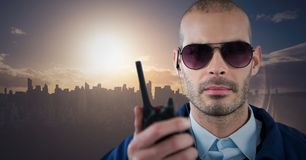 Φρουρά ασφάλειας με την ομιλούσα ταινία walkie ενάντια στον ορίζοντα και το ηλιοβασίλεμα Στοκ Εικόνες