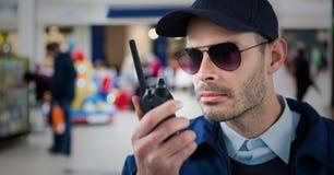 Φρουρά ασφάλειας με την ομιλούσα ταινία walkie ενάντια στο μουτζουρωμένο εμπορικό κέντρο Στοκ Φωτογραφία