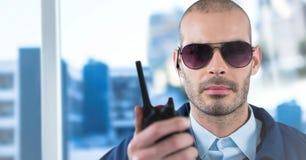 Φρουρά ασφάλειας με την ομιλούσα ταινία walkie ενάντια στο μουτζουρωμένο παράθυρο που παρουσιάζει πόλη Στοκ Εικόνες