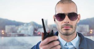 Φρουρά ασφάλειας με την ομιλούσα ταινία walkie ενάντια στο μουτζουρωμένο ορίζοντα Στοκ Εικόνες