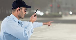 Φρουρά ασφάλειας με την ομιλούσα ταινία walkie που δείχνει ενάντια στη μουτζουρωμένη οδό Στοκ Εικόνα