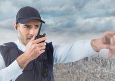 Φρουρά ασφάλειας με την ομιλούσα ταινία walkie που δείχνει ενάντια στον ορίζοντα και τα σύννεφα Στοκ Φωτογραφίες