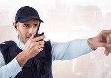 Φρουρά ασφάλειας με την ομιλούσα ταινία walkie που δείχνει ενάντια στον εξασθενισμένο ορίζοντα Στοκ Εικόνες