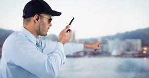 Φρουρά ασφάλειας με την ομιλούσα ταινία walkie που δείχνει ενάντια στο μουτζουρωμένο ορίζοντα Στοκ Φωτογραφία