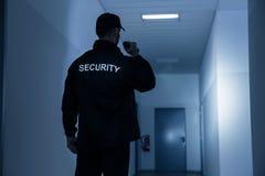 Φρουρά ασφάλειας με το φακό στην οικοδόμηση του διαδρόμου Στοκ Εικόνες
