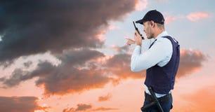 Φρουρά ασφάλειας που και που μιλά στην ομιλούσα ταινία walkie αντιμετωπίζοντας προς τον ουρανό Στοκ Φωτογραφία