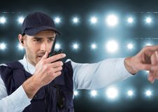 Φρουρά ασφάλειας που μιλά με walkie-talkie και που δείχνει κάτι σε μια ελαφριά πλάτη Στοκ Φωτογραφίες