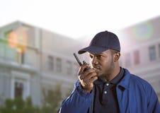 φρουρά ασφάλειας που μιλά με walkie-talkie μπροστά από ένα κτήριο στοκ εικόνες