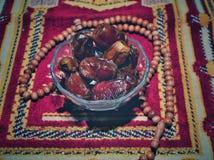 Φρούτα ή Kurma ημερομηνιών στο κύπελλο που απομονώνεται στο υπόβαθρο κουβερτών προσευχής στοκ εικόνα