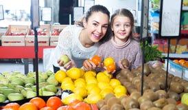 Φρούτα αγοράς γυναικών και μικρών κοριτσιών Στοκ Φωτογραφία