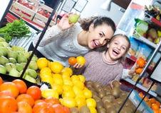 Φρούτα αγοράς γυναικών και μικρών κοριτσιών Στοκ Εικόνες