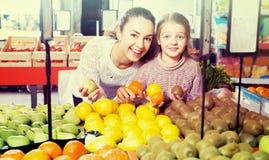 Φρούτα αγοράς γυναικών και μικρών κοριτσιών Στοκ Εικόνα