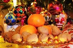 Φρούτα και καρύδια με το χριστουγεννιάτικο δέντρο στο οπίσθιο τμήμα. Στοκ Φωτογραφία