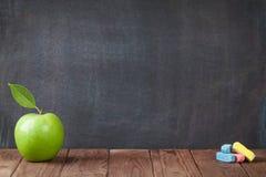 Φρούτα και κιμωλίες της Apple στον πίνακα τάξεων Στοκ φωτογραφία με δικαίωμα ελεύθερης χρήσης