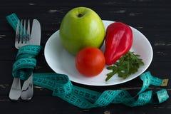 Φρούτα και λαχανικά στο πιάτο με τη μέτρηση της ταινίας στο ξύλινο υπόβαθρο Στοκ φωτογραφία με δικαίωμα ελεύθερης χρήσης