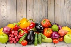 Φρούτα και λαχανικά σωρών στον ξύλινο πίνακα στο υπόβαθρο ξύλινο Στοκ Φωτογραφία