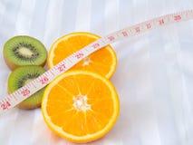 Φρούτα και πορτοκάλι ακτινίδιων με τη μέτρηση της ταινίας στο κρεβάτι στοκ εικόνα