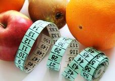 Φρούτα και ταινία μέτρησης στο άσπρο υπόβαθρο Στοκ εικόνα με δικαίωμα ελεύθερης χρήσης
