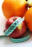 Φρούτα και ταινία μέτρησης στο άσπρο υπόβαθρο Στοκ εικόνες με δικαίωμα ελεύθερης χρήσης