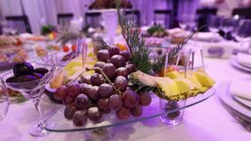 Φρούτα και τρόφιμα στον πίνακα συμποσίου στο εστιατόριο, τα κομμάτια του ανανά και τις δέσμες των σταφυλιών στον πίνακα συμποσίου απόθεμα βίντεο